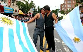 Two men celebrate while holding the flags of Uruguay and Argentina, the first two Latin American nations to legalize gay marriage.